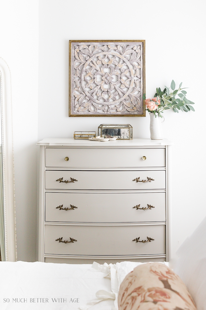 Putty colored dresser with scroll art on wall with flowers.