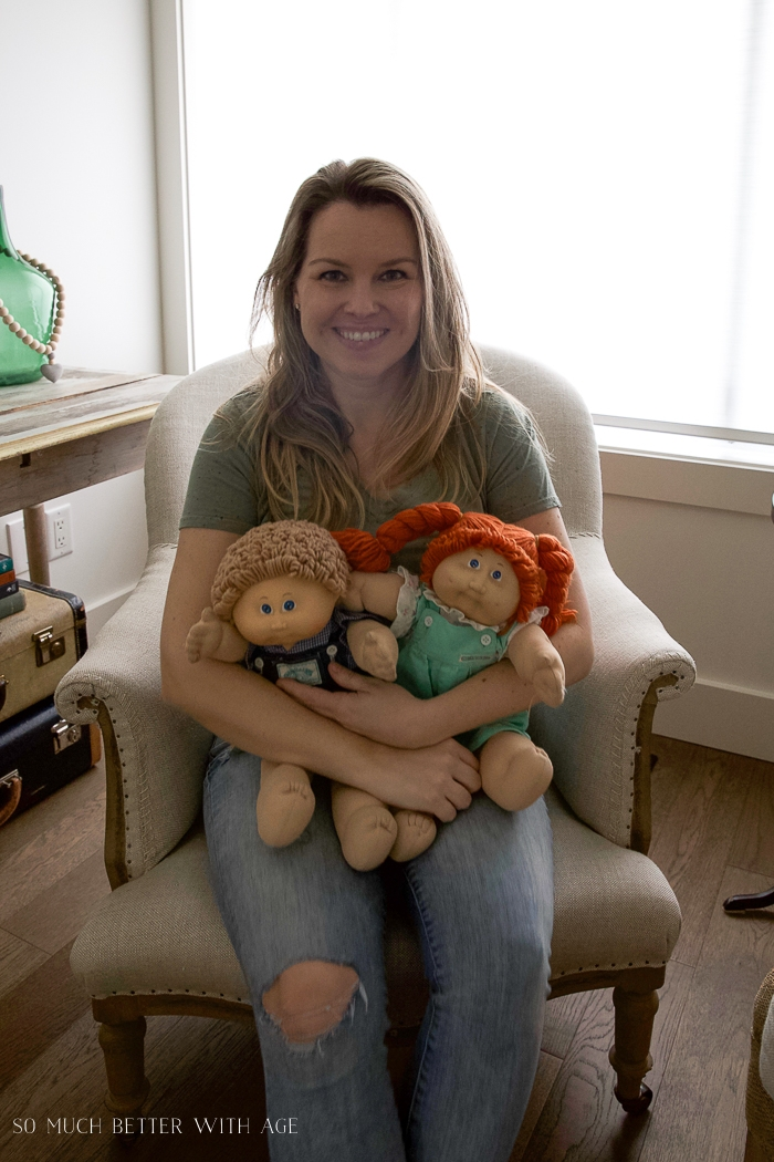 Woman holding Cabbage Patch Kids.