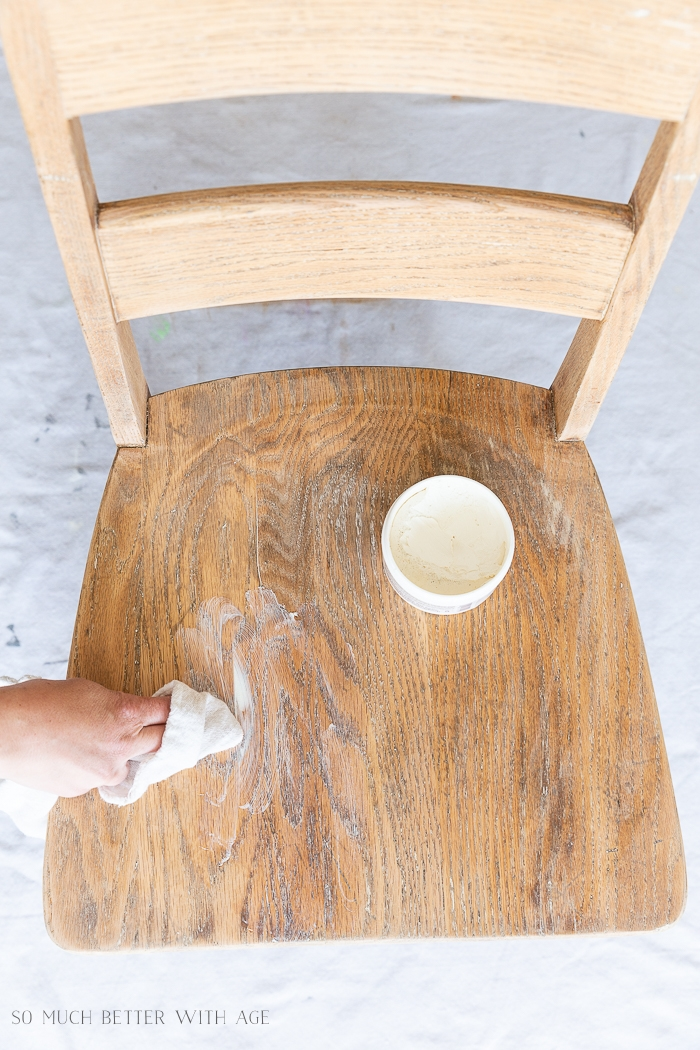Wiping in white wax on a wooden chair.