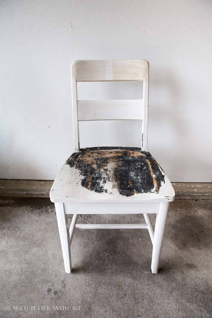 White chair with paint coming off the seat.