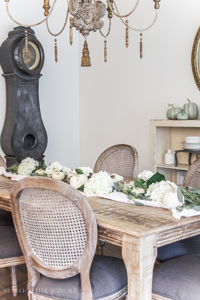 The wooden dining room table with a floral and white pumpkin runner.