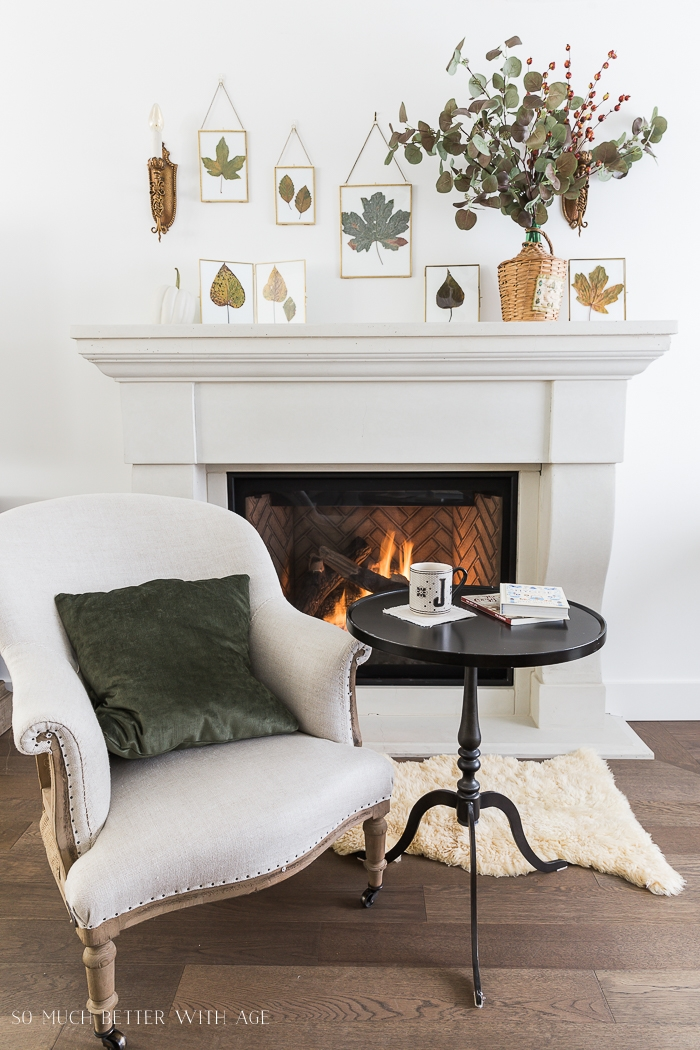 Framed leaves above mantel with cozy chair and side table in front of fire.