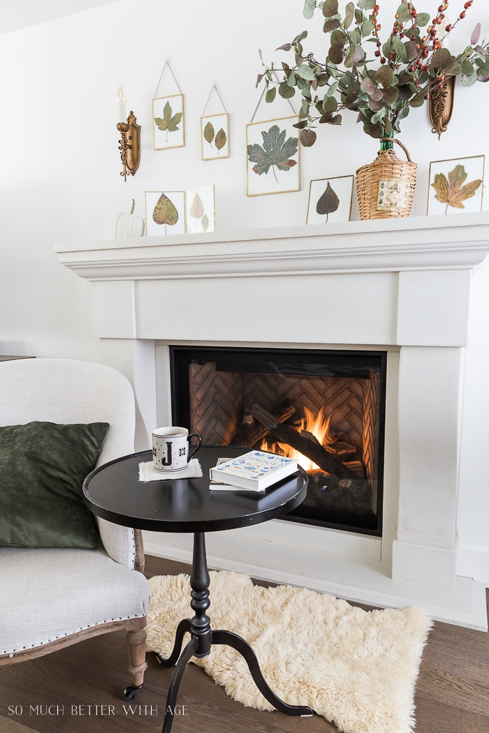 Chair and table in front of cozy fireplace.