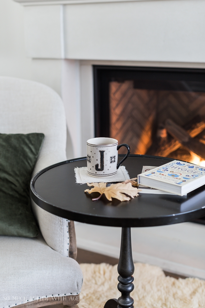 Mug with books on small table by chair in front of a fireplace.