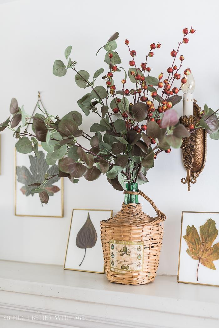 Eucalyptus leaves in vase on mantel.