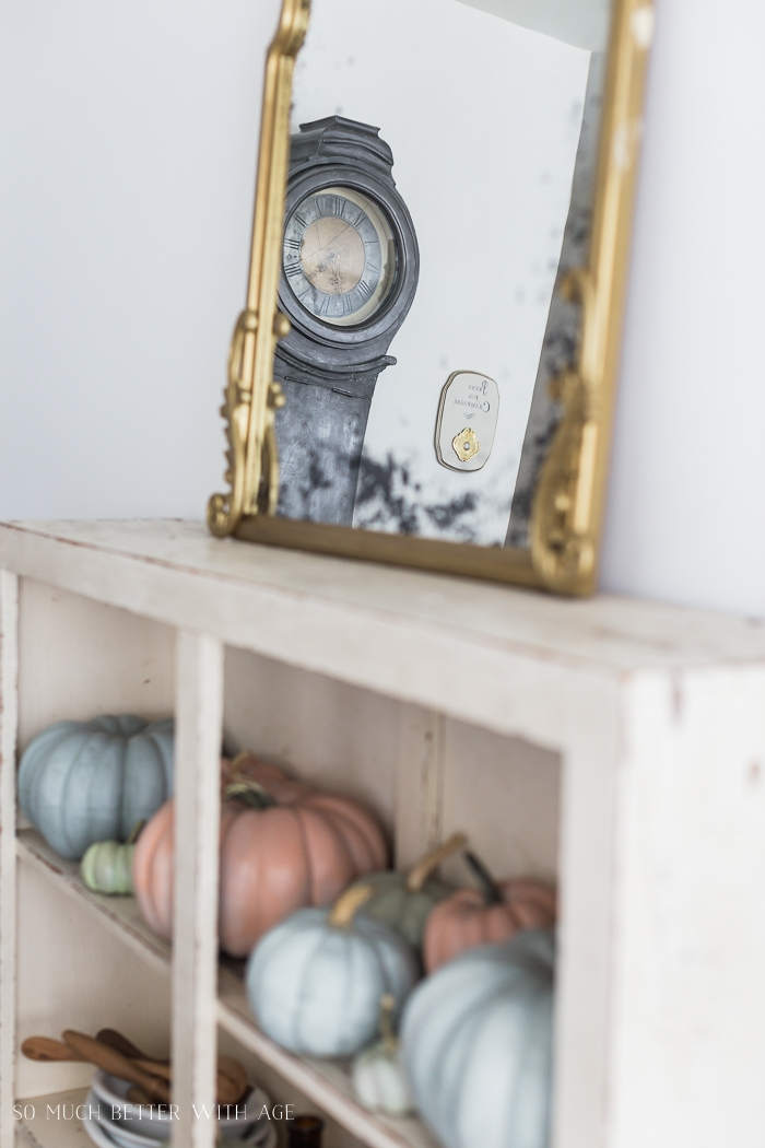 View of tall clock in a mirror and pumpkins on a shelf.