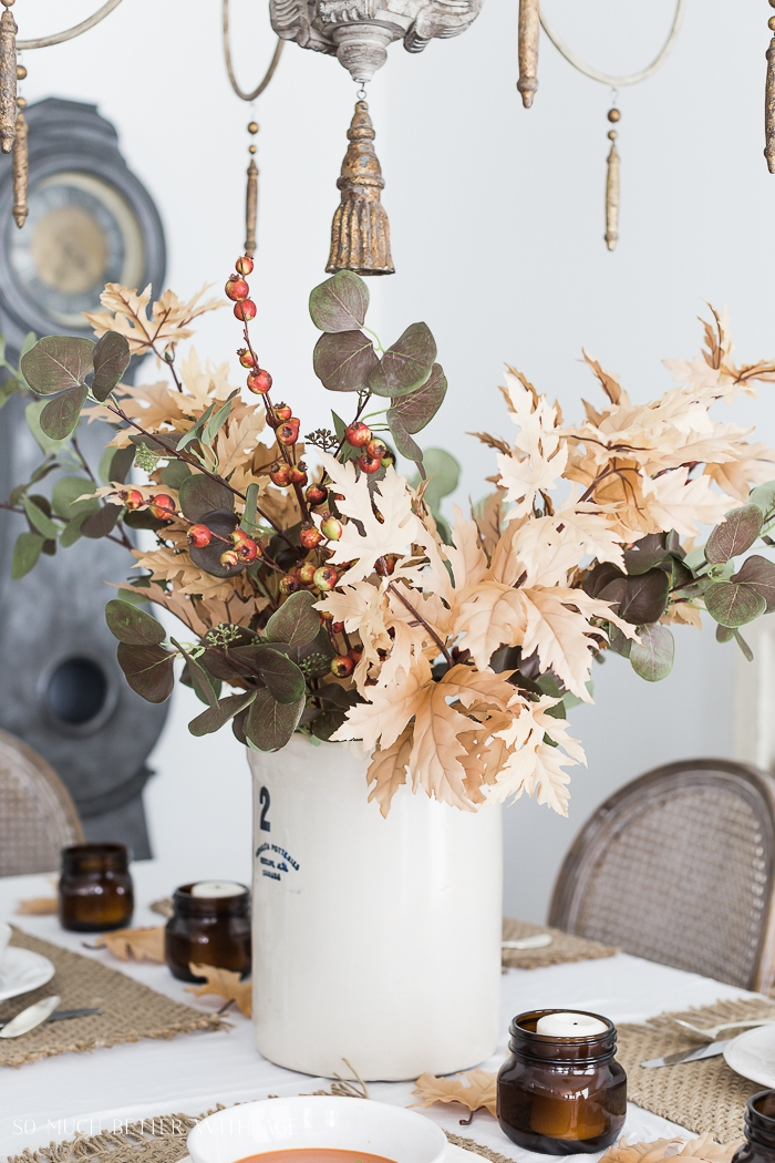 Fall leaves and eucalyptus in big crock on dining table with mora clock in background.