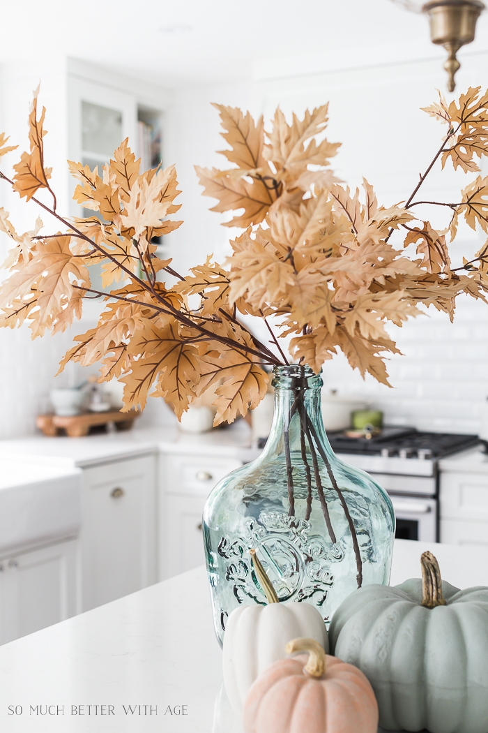 Light colored fall leaves in light green glass vase.