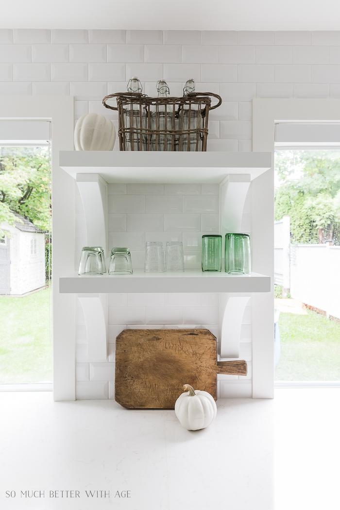 White kitchen open shelves with some white pumpkins.