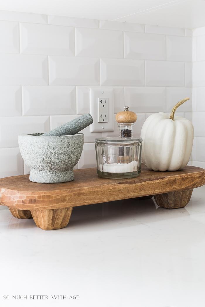 White pumpkin on wooden pedastal sitting on kitchen countertop.