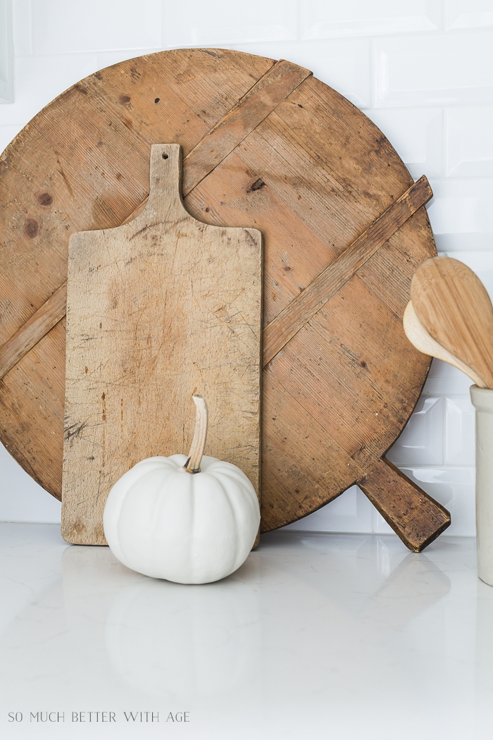 French bread boards leaning against backsplash with a white pumpkin.