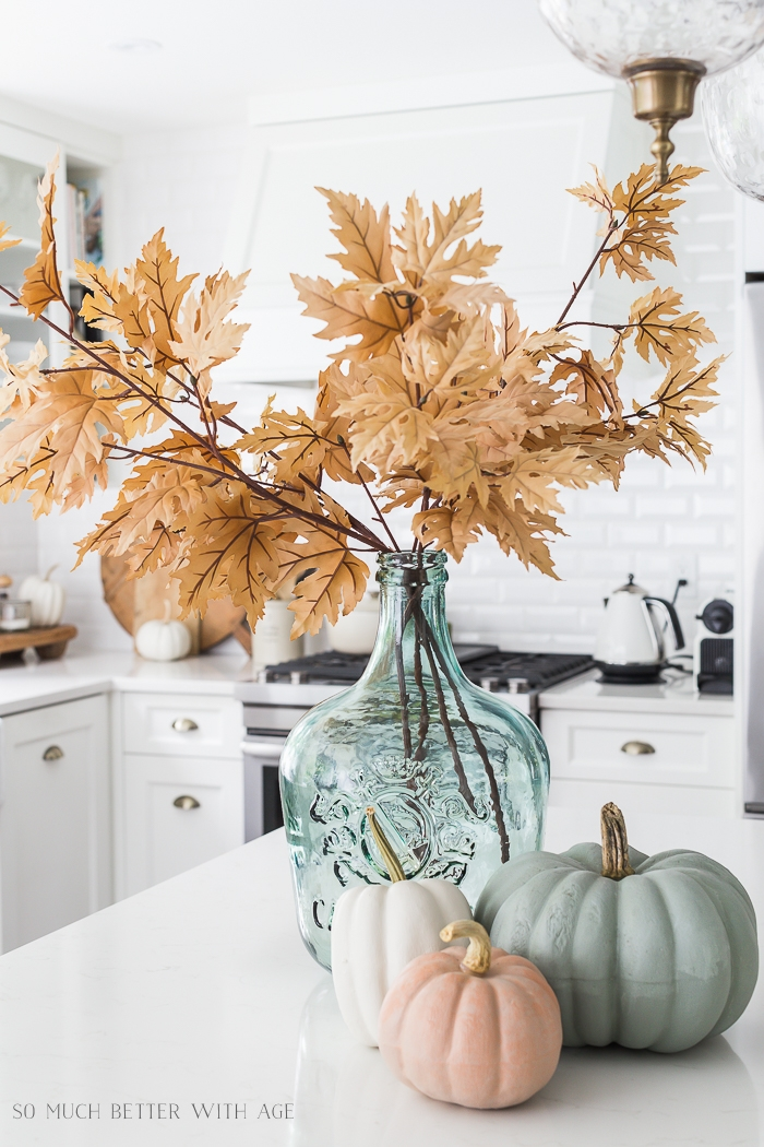 Tan fall leaves in aqua glass vase or demijohn with realistic painted pumpkins.