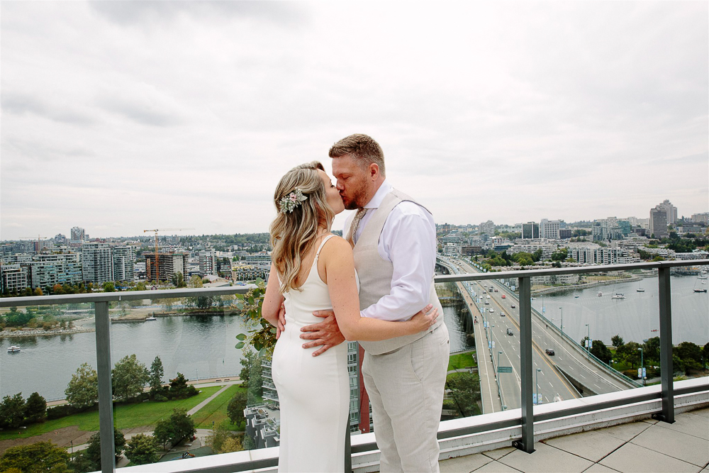 The couple kissing on the rooftop.