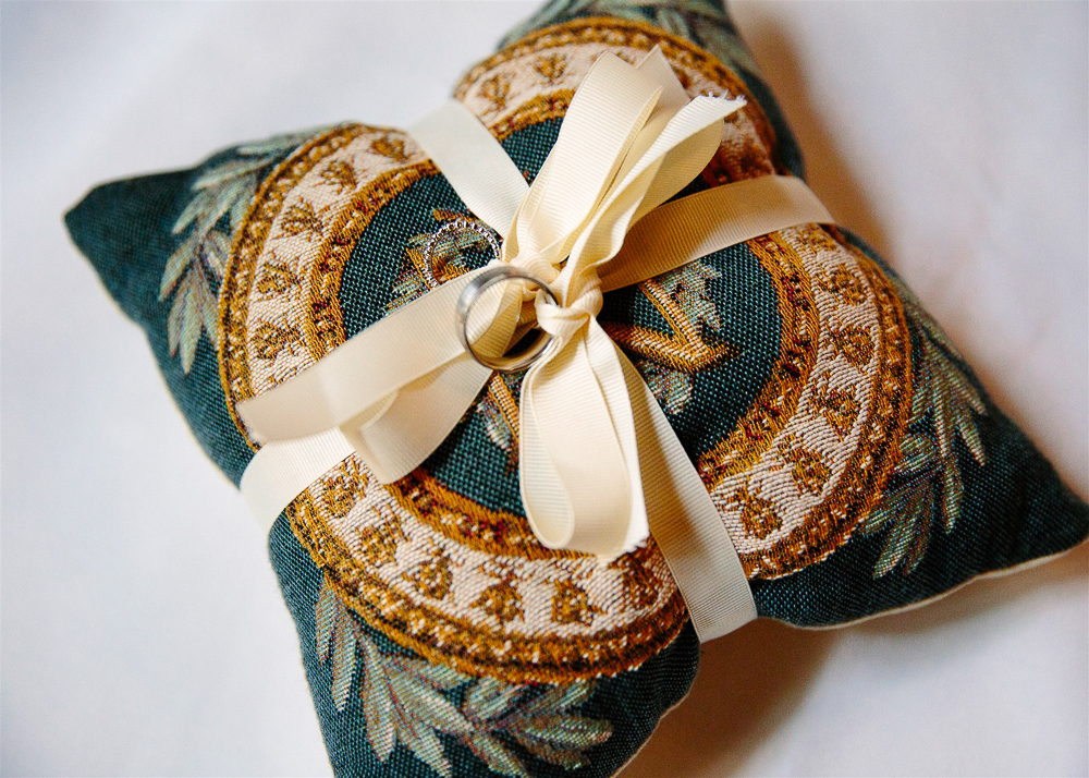 An embroidered pillow with the rings on it.