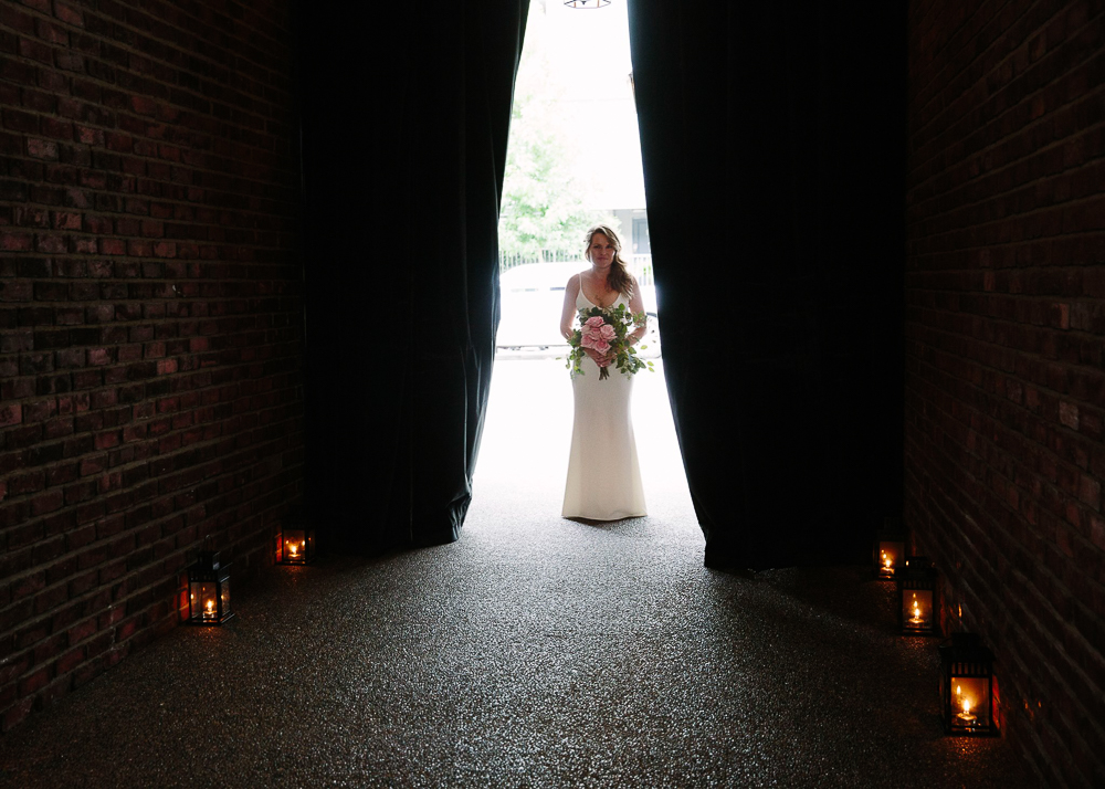Jamie standing at the end of the aisle waiting to walk with curtains parted.