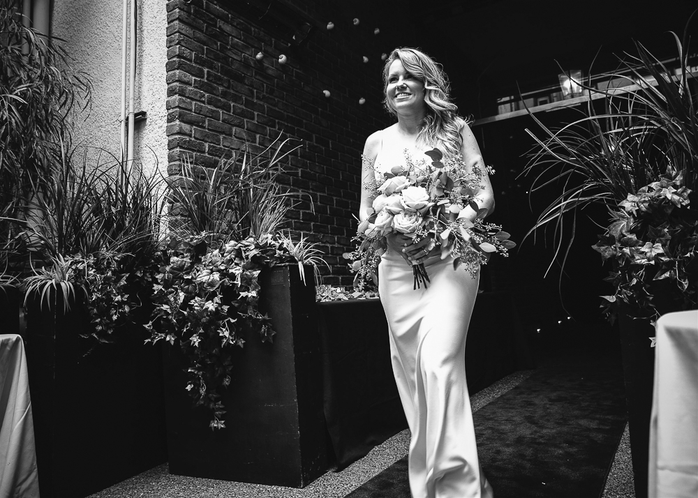 Walking down the aisle with a big smile.
