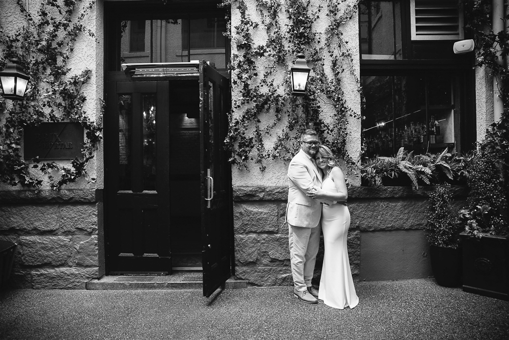 Jamie and Aaron hugging in front of a stone wall.