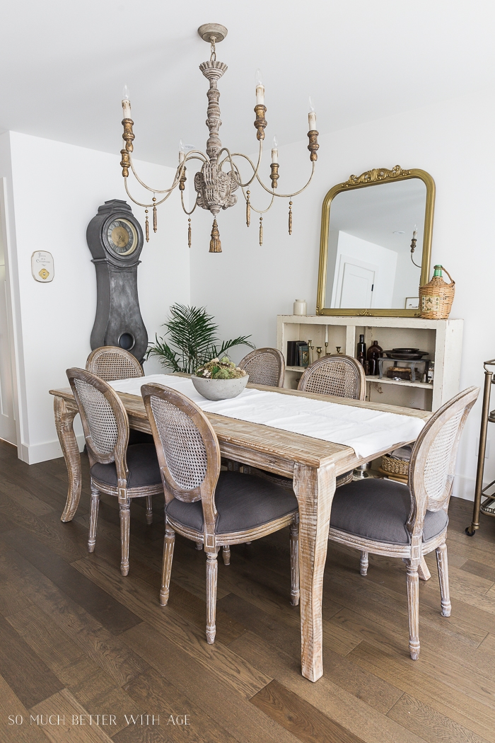 Dining room with large French chandelier and clock.