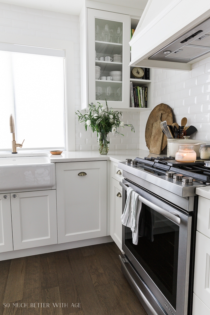 White kitchen with gold faucet and bouquet of flowers.