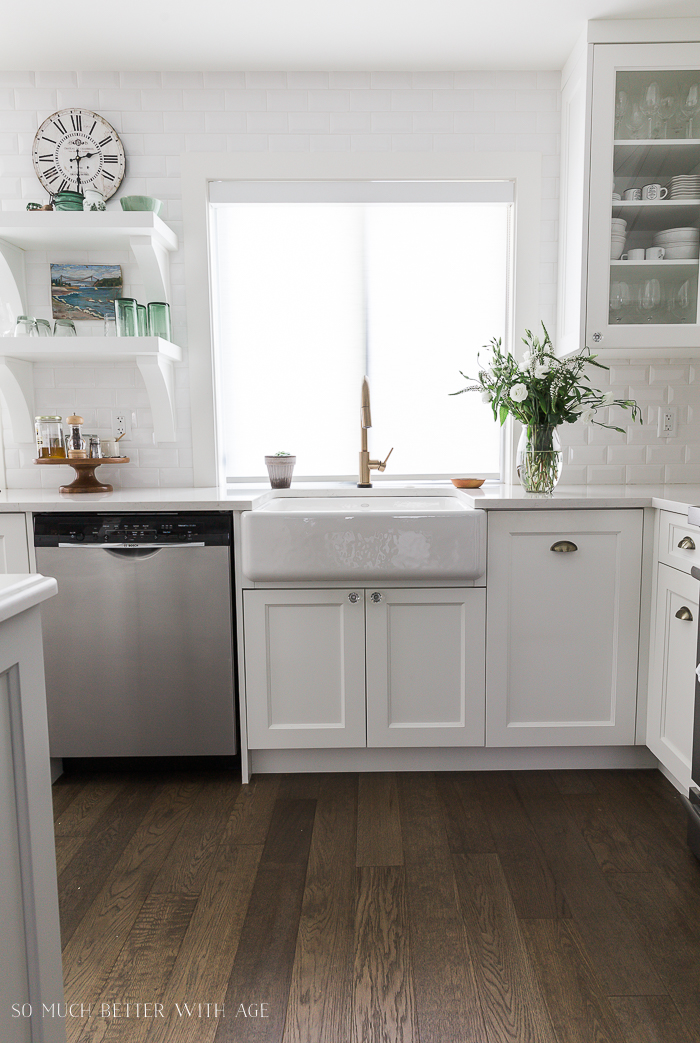 White kitchen with open shelving and white floral arrangement.