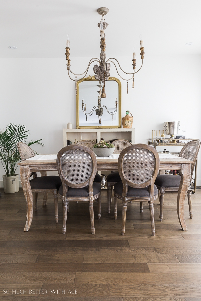 Large chandelier in dining room with table and chairs in French style.