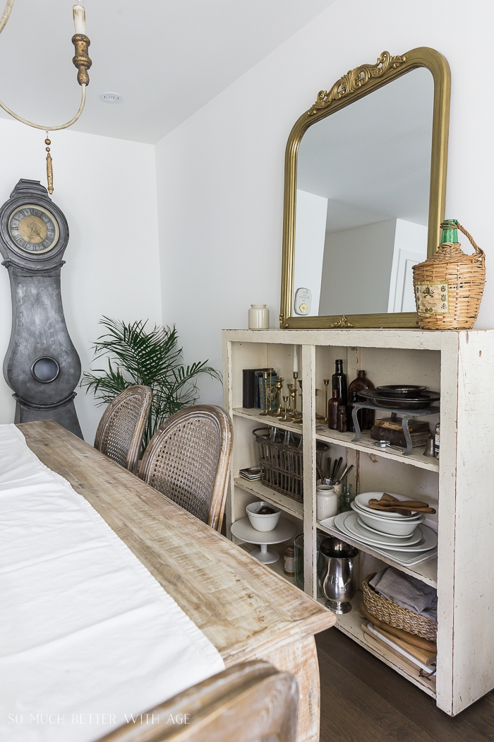 Gold mirror on bookshelf with large clock on wall.