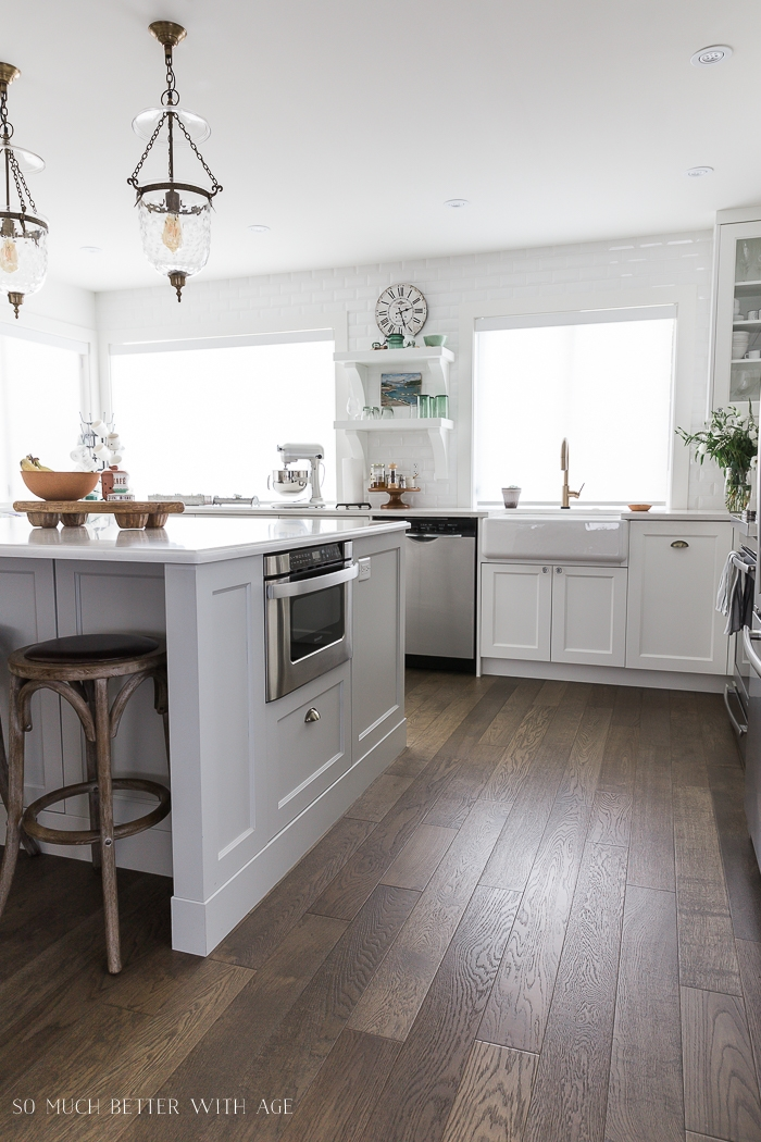 White kitchen with large windows and big island.