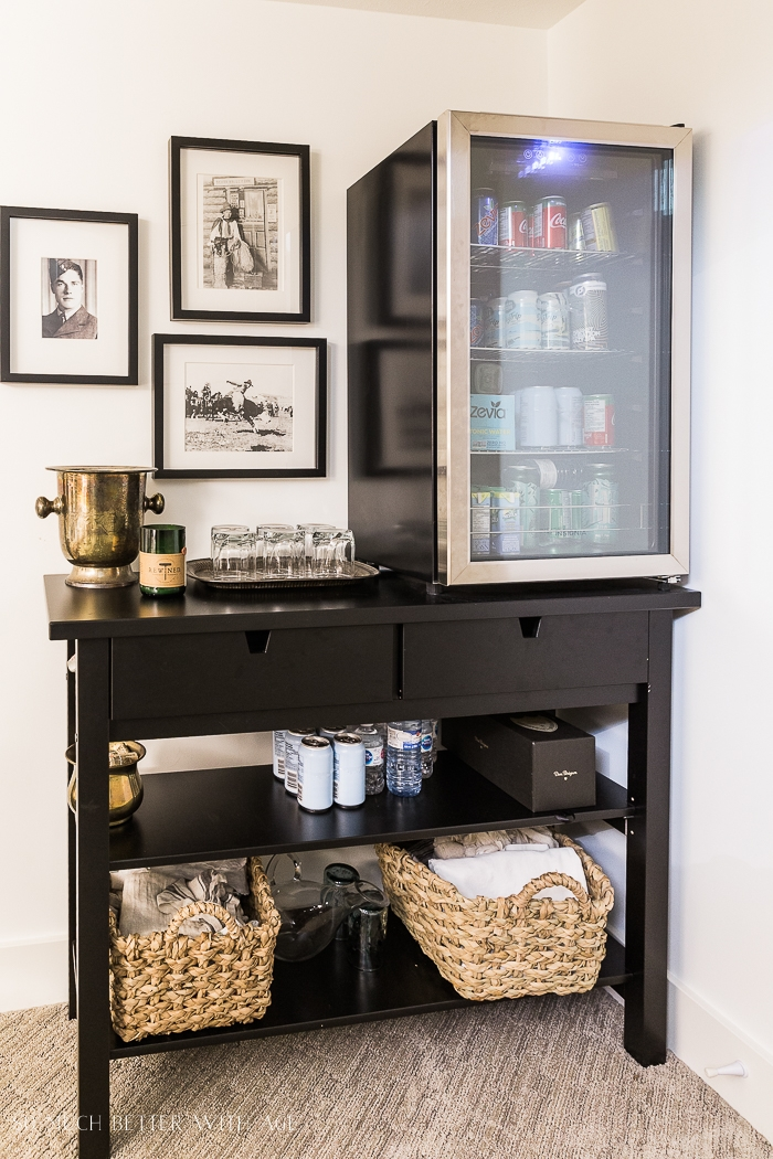 Bar fridge on console table with baskets and black photos on wall.