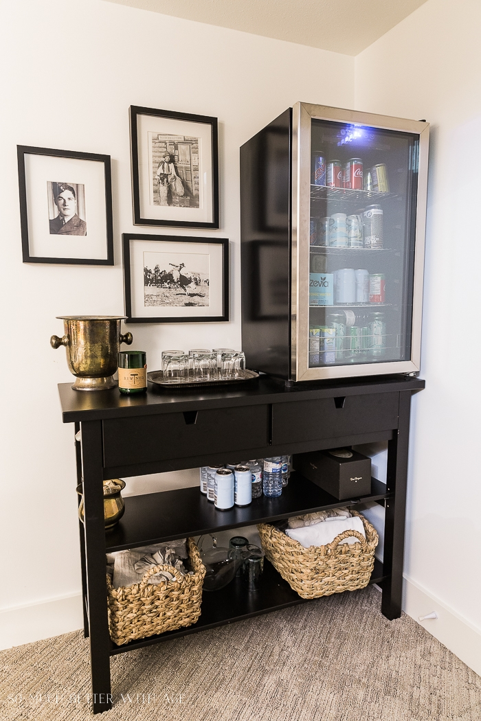 Bar area with bar fridge and black frames.