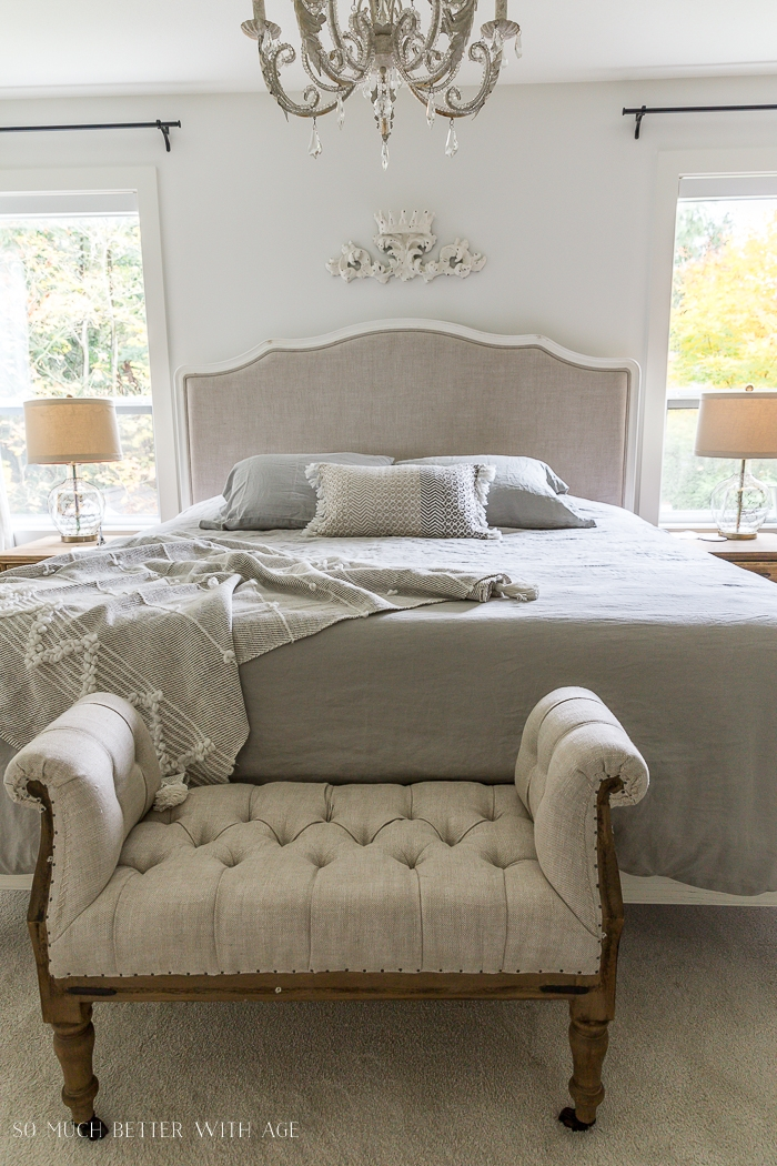 Tufted linen ottoman with upholstered bed in master bedroom with 2 lamps on either side.