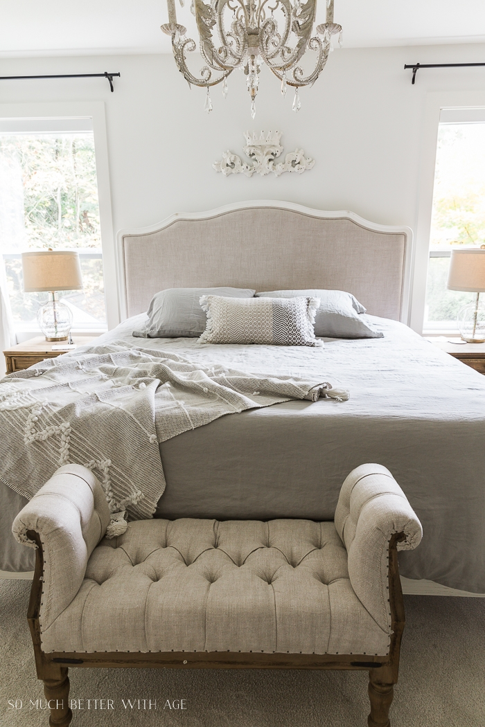 Upholstered bed with tufted ottoman at foot of it.