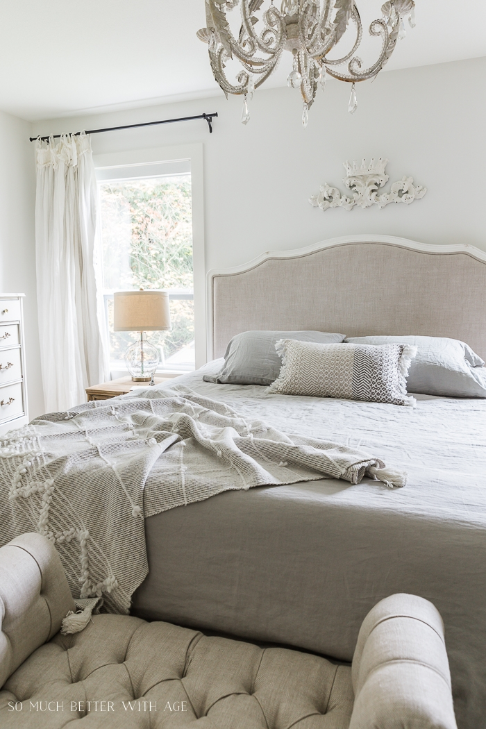 White bedroom decorated with linen upholstered bed and tufted ottoman.