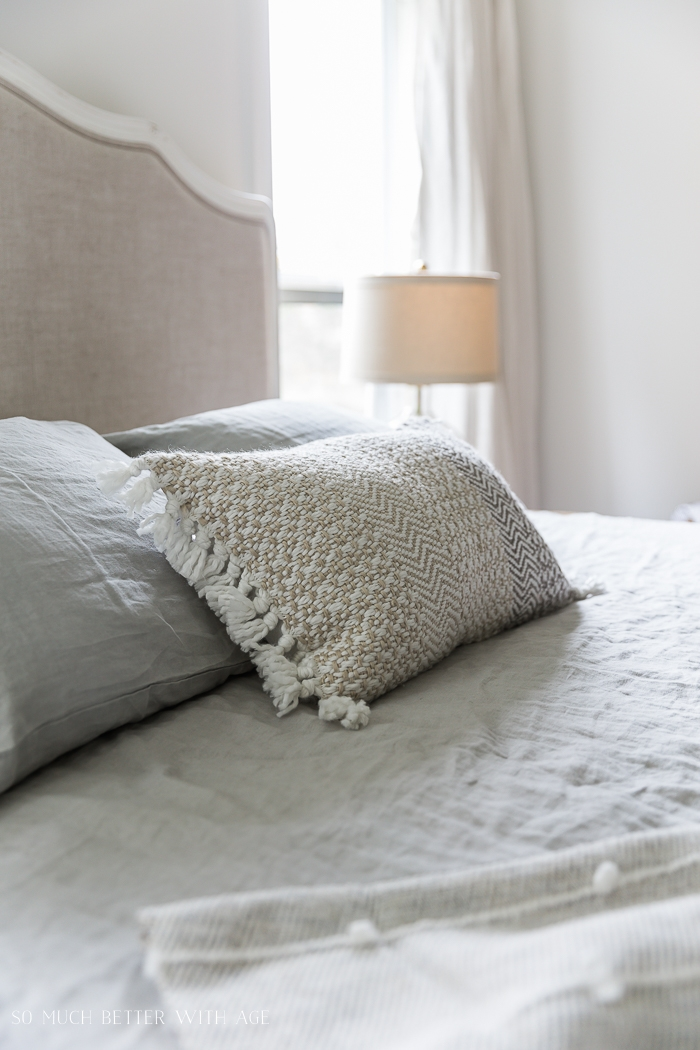 Pillow on bed with lamp in a white room.