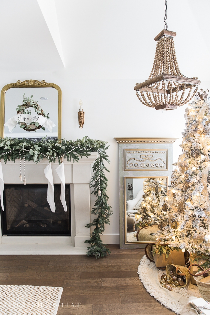 White fireplace mantel with white stockings hanging on the mantel, a garland of greenery on the mantel trailing onto the floor, a gold and White Christmas tree, and a French inspired mirror on the floor beside the tree.
