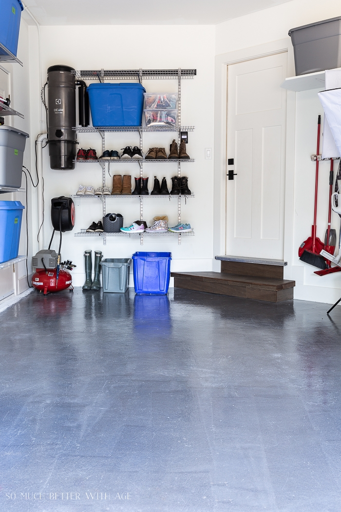 Organized tidy garage with shoes on shelving rack.