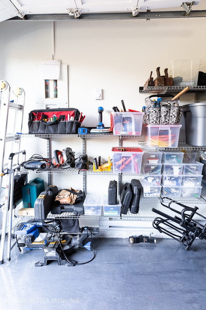 Tools and bins on wall shelving unit.