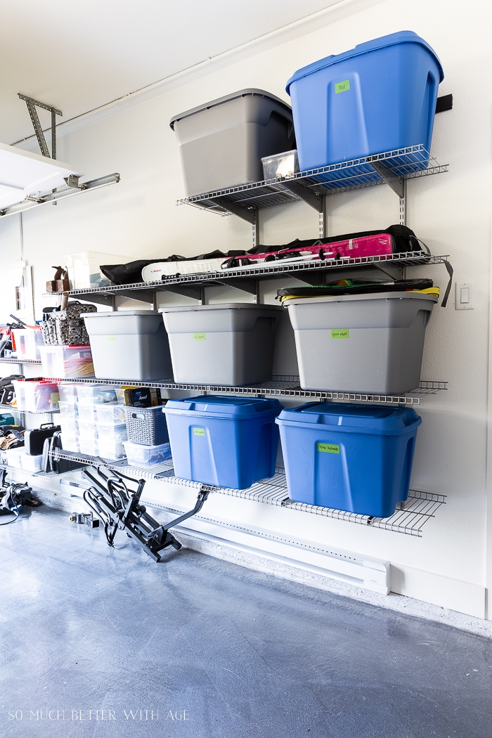 Large plastic storage bins on wall shelving unit in garage.