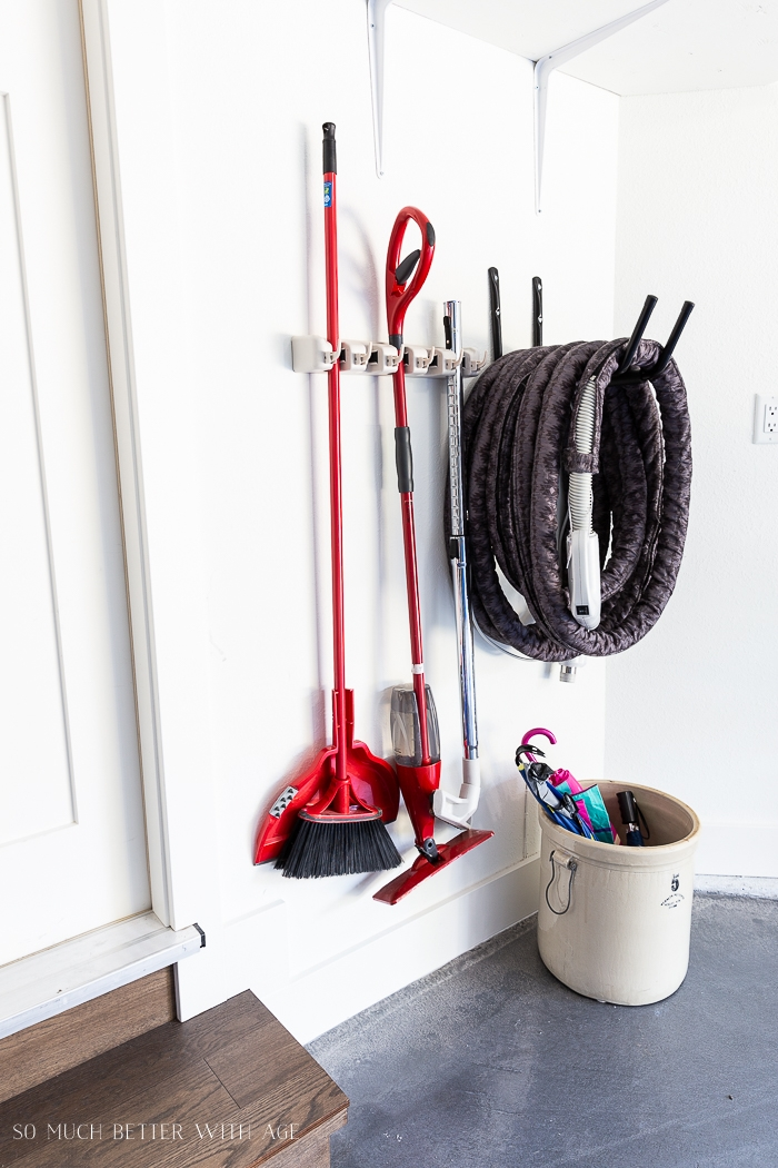 Broom wall rack and holder for vacuum hose on wall.