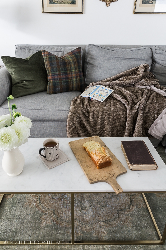 Cozy couch with mug of tea and cake.