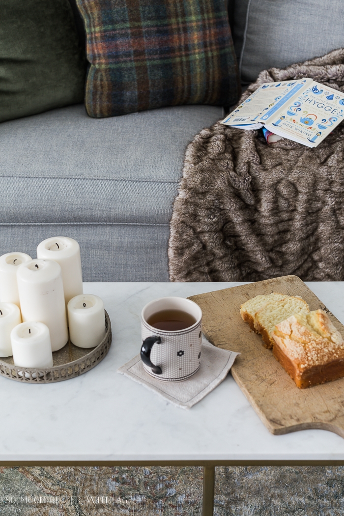Cozy scene with couch, blanket, cake, candles and tea.