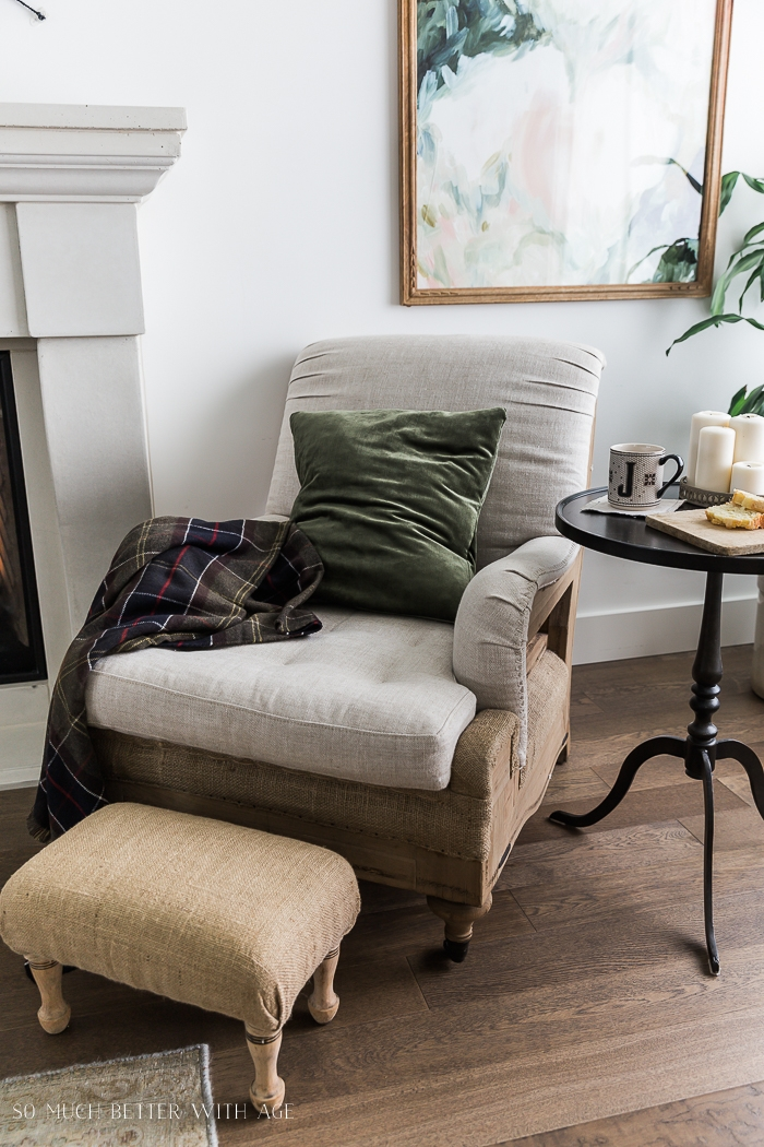 Cozy chair with plaid throw and green velvet pillow.