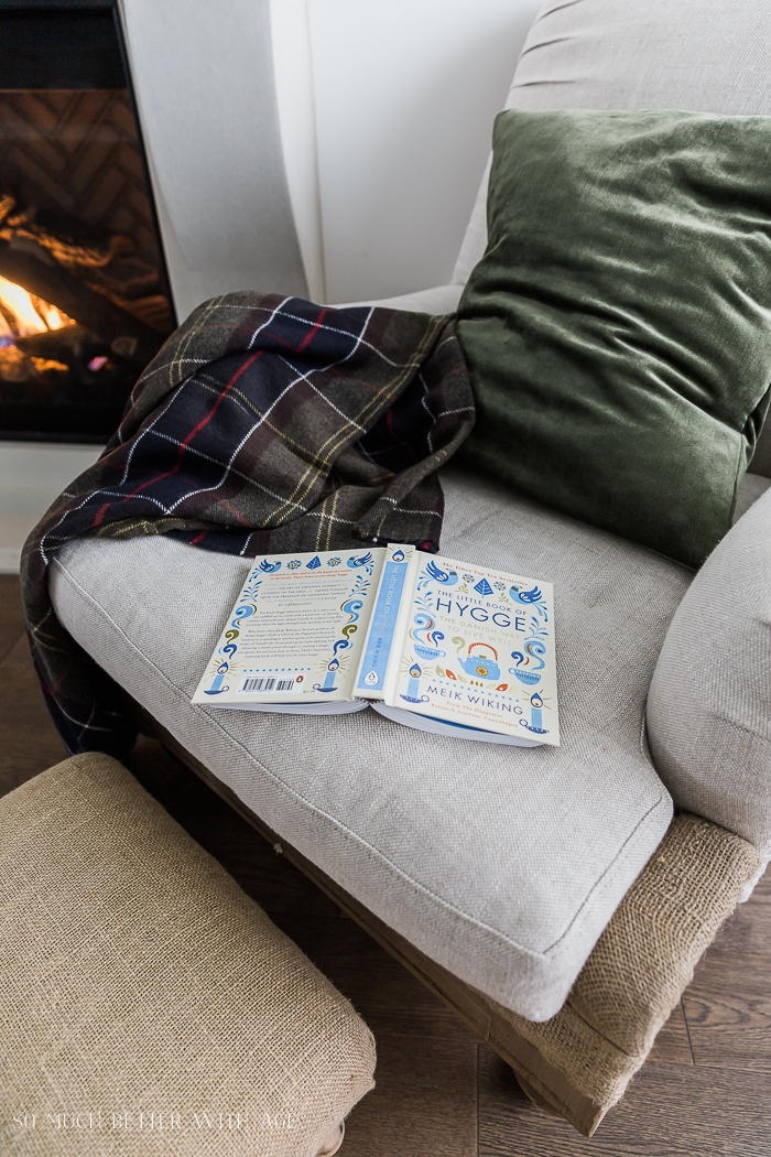 Cozy chair, book and throw by a fireplace.