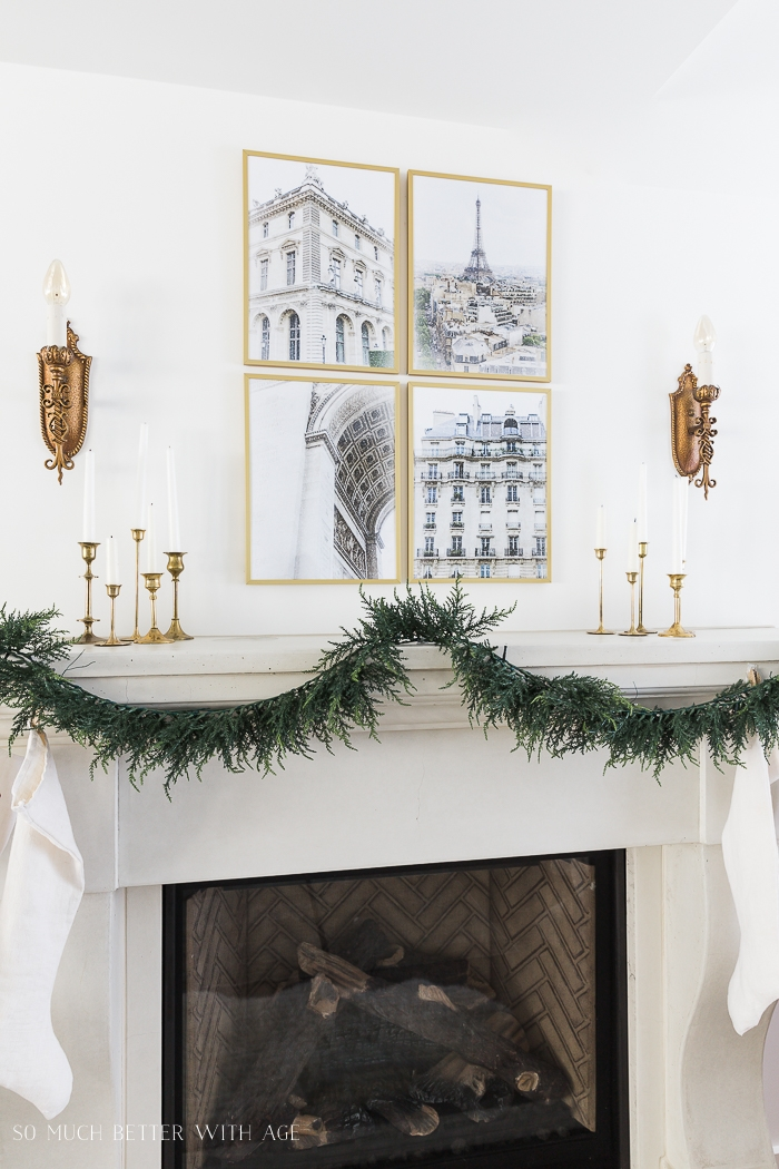 Green garland on mantel with four Paris images in frames.