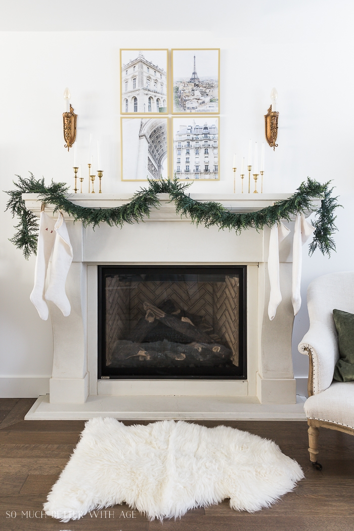 Four Paris framed photos on wall above mantel with garland and stockings.
