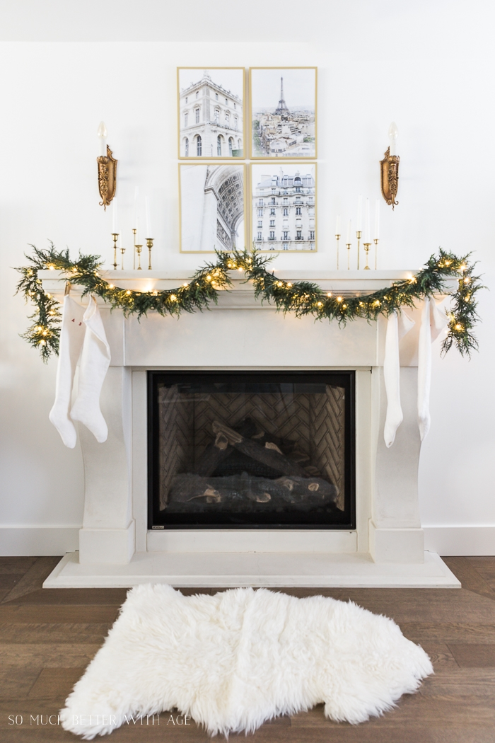 Garland with lights on mantel with four gold pieces of artwork and brass candlesticks.