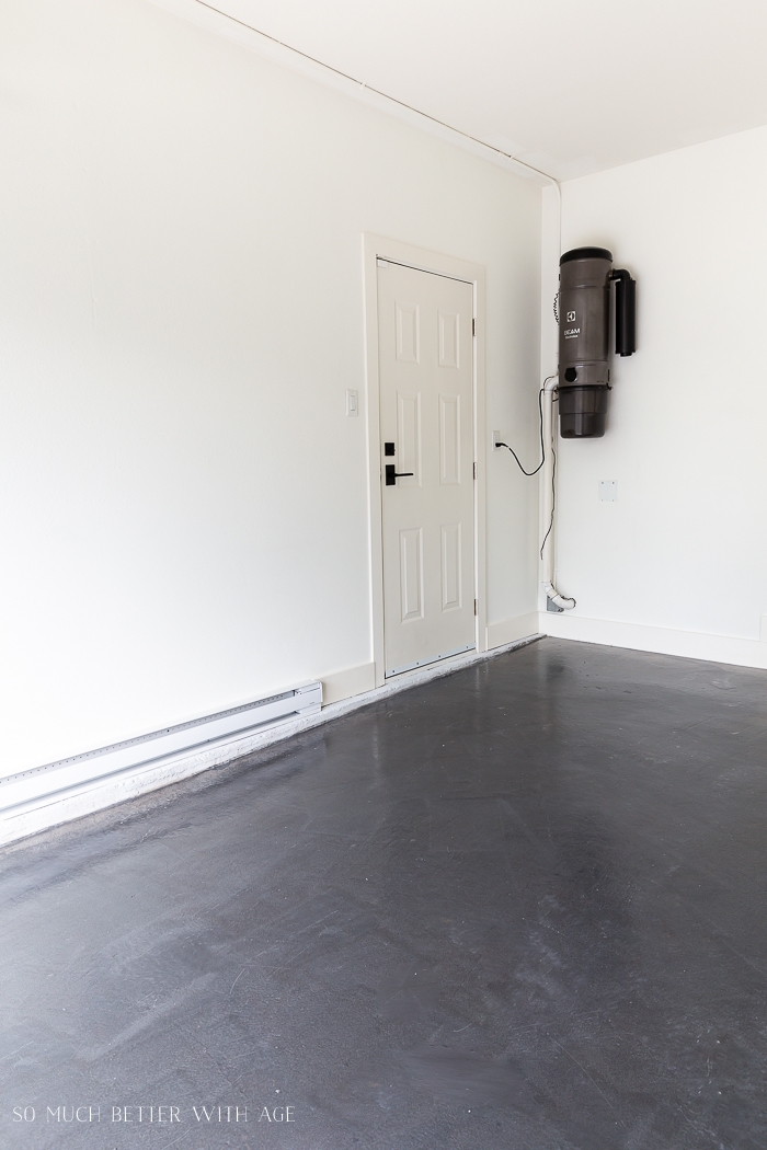 Empty garage with vacuum canister in corner.