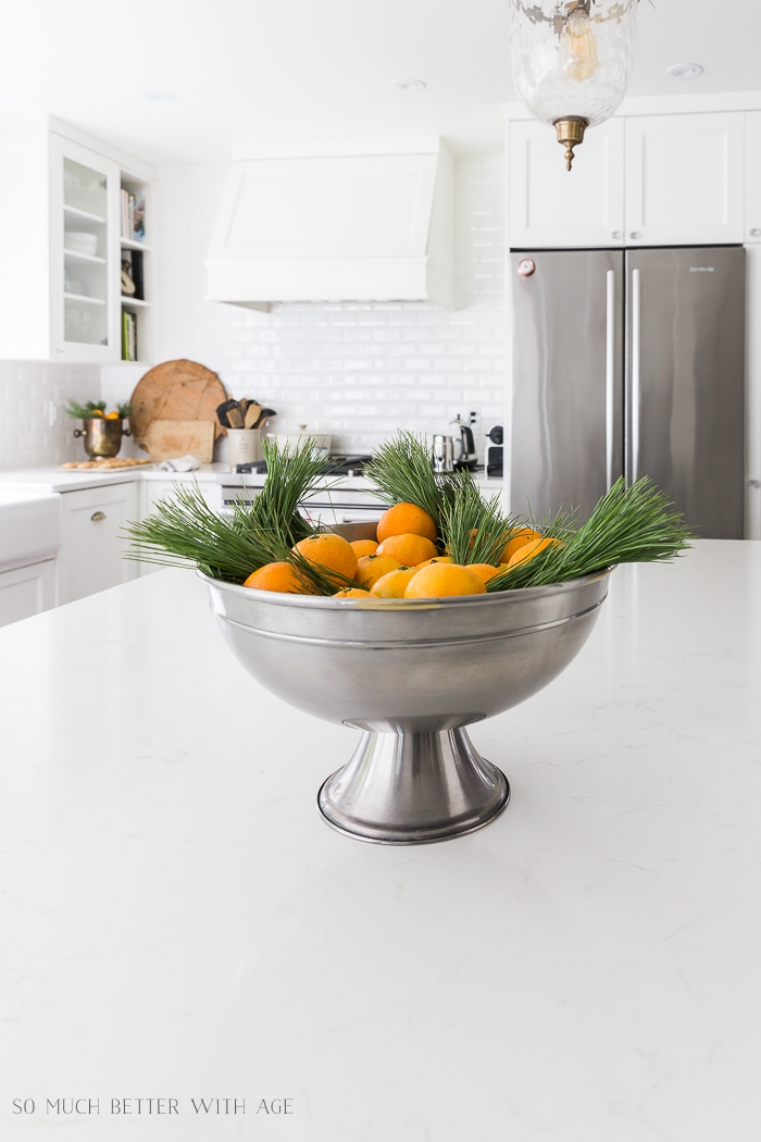 Oranges and greenery in big silver bowl on kitchen counter.