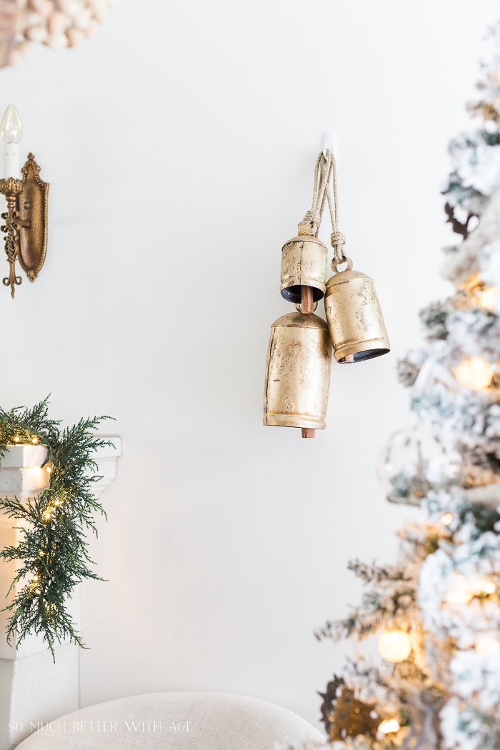 Brass bells hanging on wall by Christmas tree.