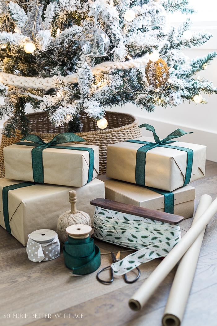 Presents wrapped with kraft paper and green bow under the tree.