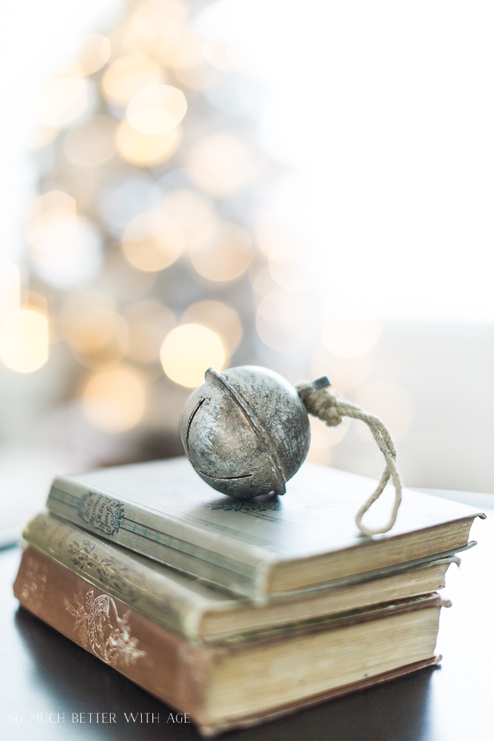 Jingle bell on old books with bokeh lights in background.